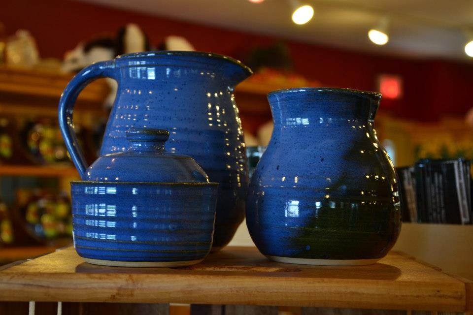 Three pieces of glossy blue pottery sit on display on a wooden shelf. The three pieces of pottery include a pitcher, a vase, and a sugar bowl.