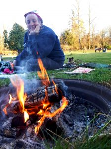 Emily is smiling while sitting on a blanket on the grass in front of a campfire. There are horses in a field in the background and a fire burning bright in the foreground.