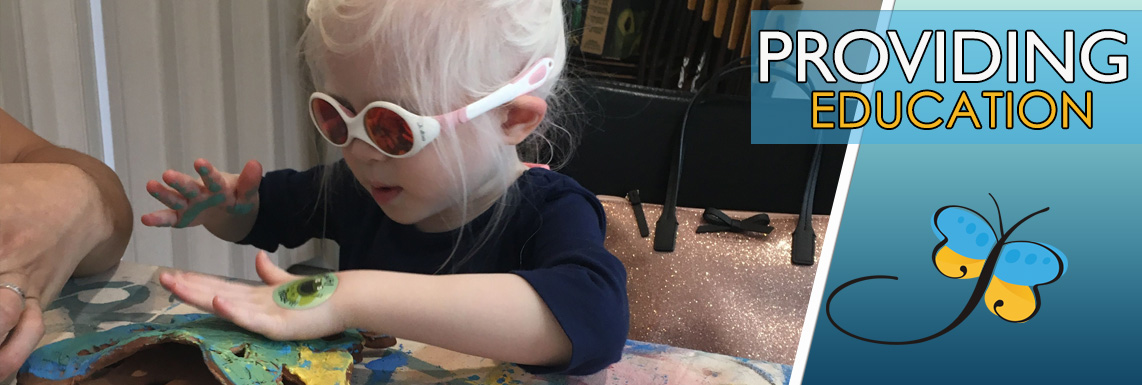 Image of a child that is partially sighted wearing sunglasses manipulating a piece of pottery with the words Providing Education floating above the image.