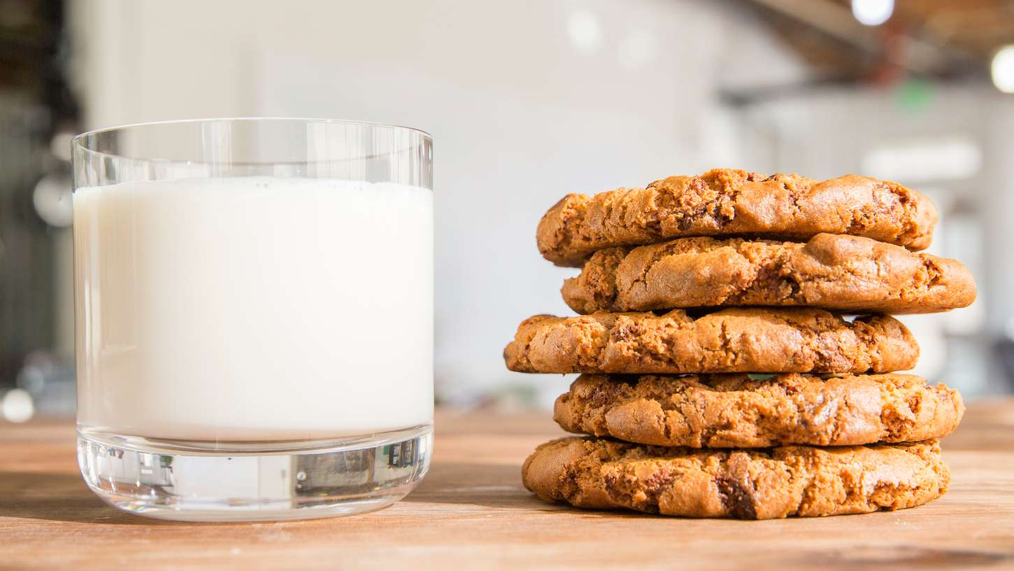 Image of a glass of milk beside a stack of freshly baked chocolate chip cookies