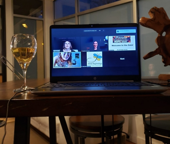 A wine glass filled with white wine sits at a table beside a laptop that has the Zoom interface open and the Harvesting Hope's hosts that include Shawn, Arran, and Emily can be seen in several video chat windows