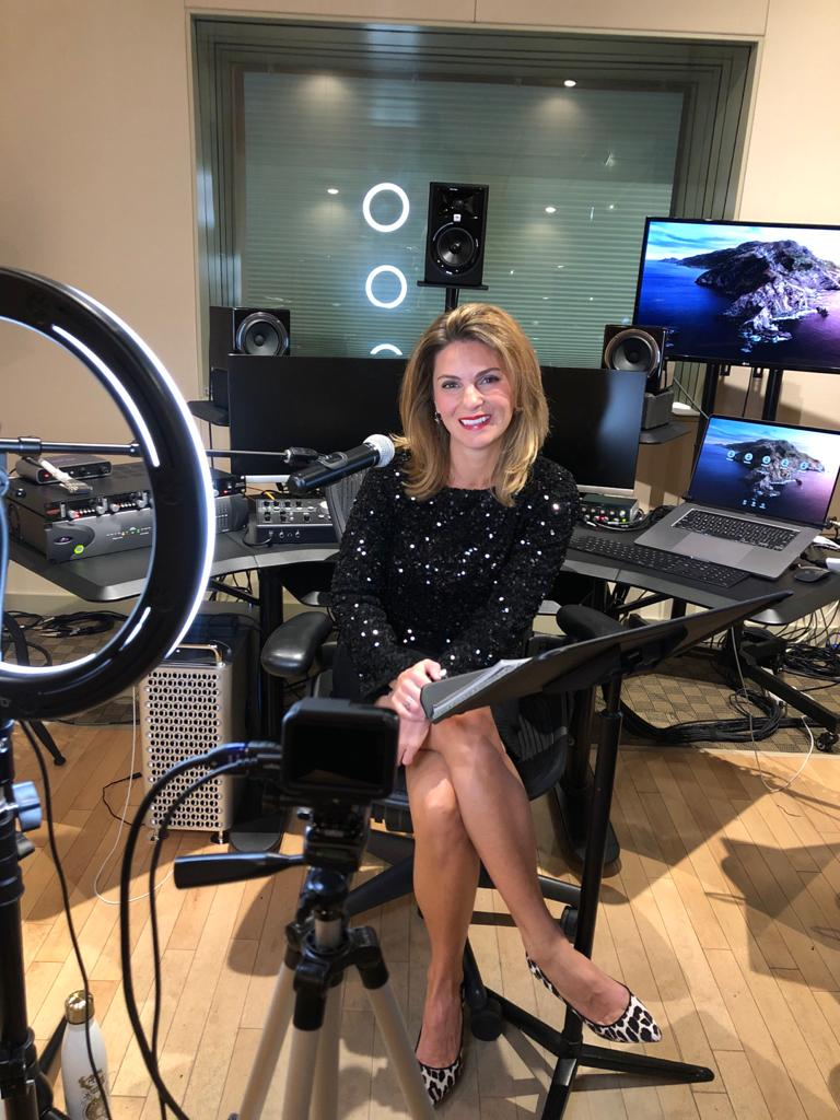 Our wonderful host for the evening, Arran Henn poses and smiles as she sits at her hosting station flanked by laptops and a microphone at the Descriptive Video Works studio.