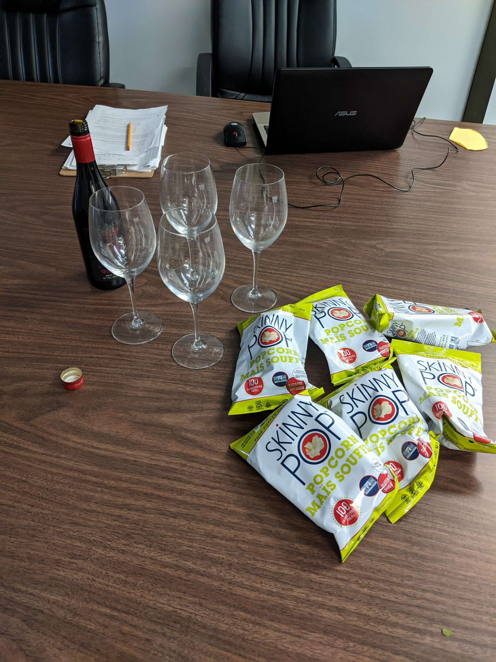 A bottle of red wine sits beside a group of four wine glasses and a pile of individual sized bags of popcorn, waiting for Blind Beginnings staff to partake.
