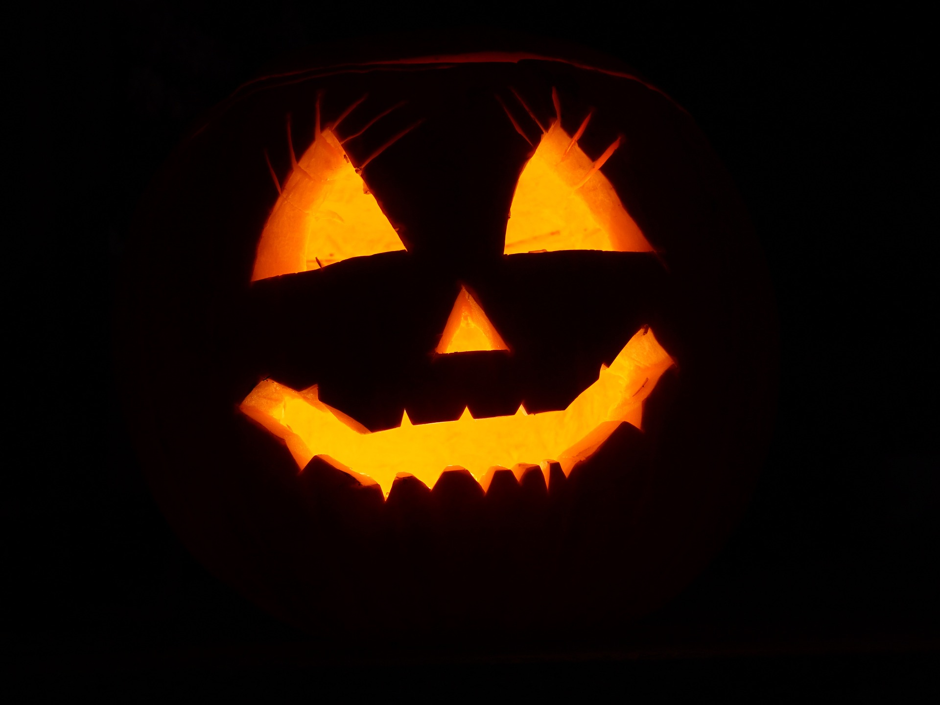 Image of a Carved Pumpkin, lit from the inside with a candle, glowing in the darkness