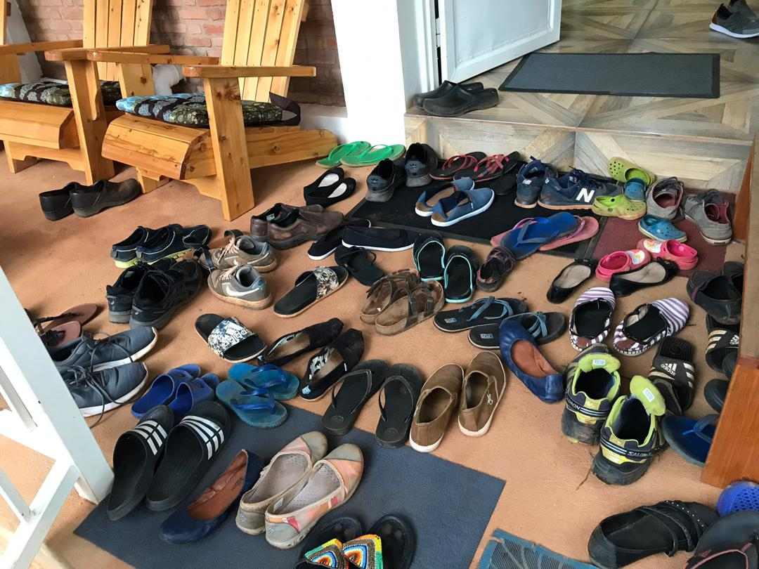 Image of a large collection of all manners of shoes piled chaotically at the doorway of a party