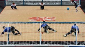 Image of the Goalball court and each team on opposite sides in front of their respective nets, which run the length of the court.
