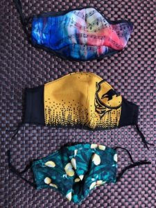 Three masks, the one on the top is multicoloured with music notes. The one in the middle is yellow with the Harry Potter Hufflepuff symbol. The one on the bottom is patterned with lemons.