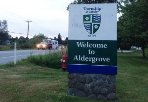 Image of the Welcome to Aldergrove sign, placed on a green patch of grass and flanked by an open Highway.