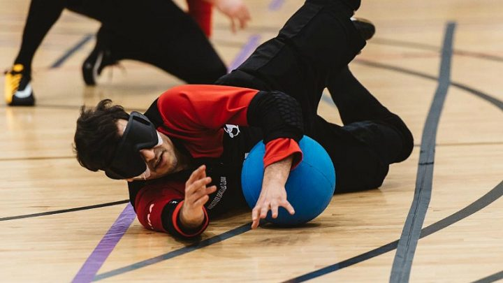 Image of a Goalball player wearing a blindfold and blocking a shot by the opposing team
