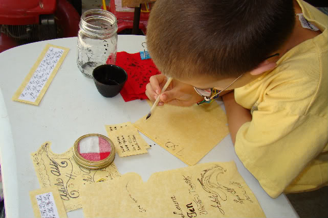 Image of a boy using a quill to write on a piece of parchment paper.