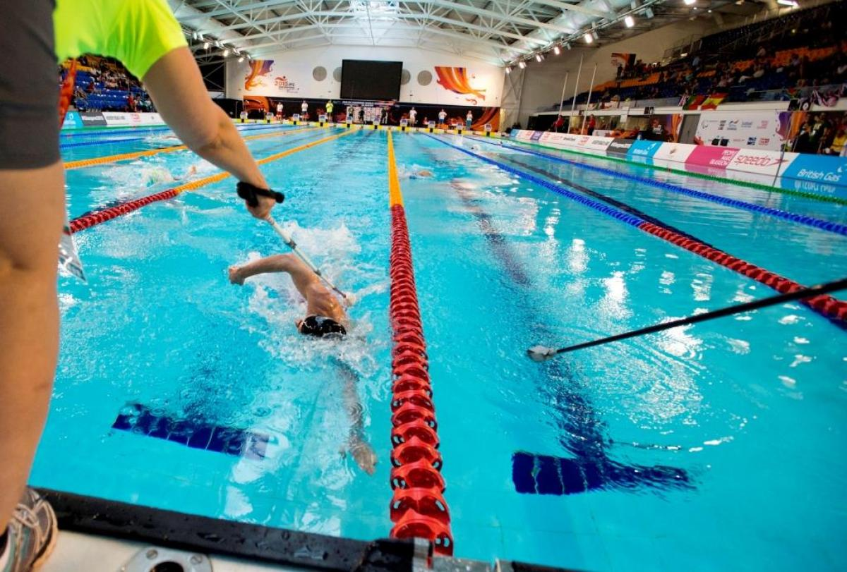 Image of a blind swimmer nearing the end of the pool and a tapper reaching out with a pole that has a soft end to alert him