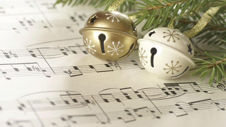 Image of sheet music underneath the green decorated branches of a Christmas Tree