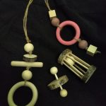 Assorted chew toys made from plain and coloured wood beads, rings and dowels on string