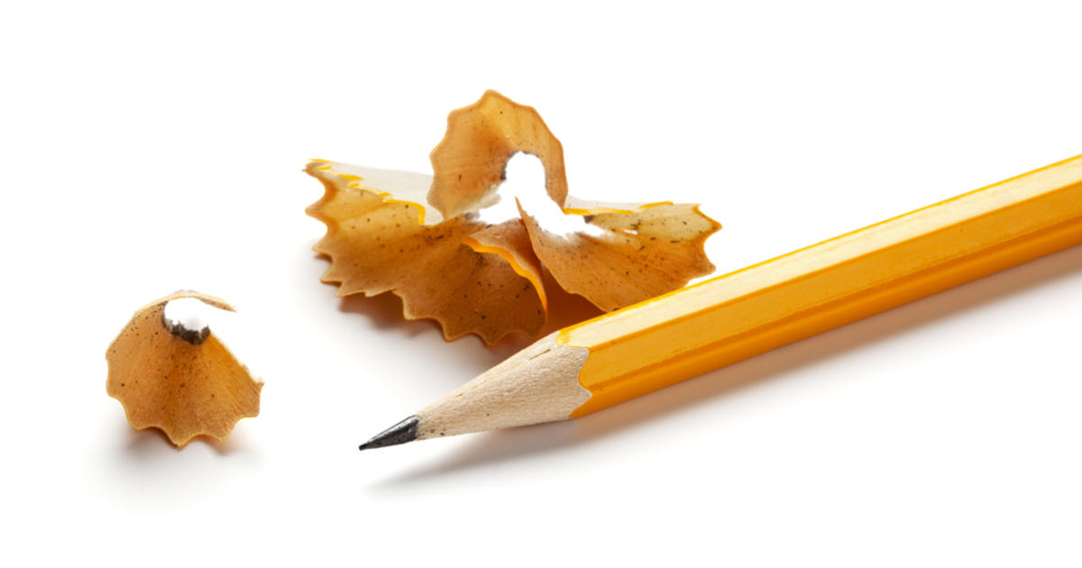 Image of a sharpened pencil against a stark white background, surrounded by pencil shavings.