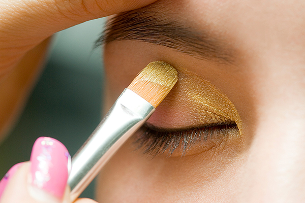 Image of a woman, her eyes closed, applying a layer of gold eyeshadow with a small brush
