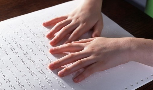 Image of a braille book open and a pair of hands gliding across a line of braille.