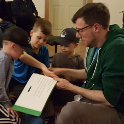 Adam sits cross-legged on the floor with a children's book open while several children gather around him in a circle as he reads during an Early Intervention Retreat.