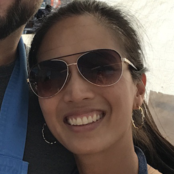 Candice, wearing sunglasses, smiles and poses for the camera.