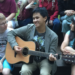 Clement picks at the strings of his acoustic guitar as he sits surrounded by Youth at one of our Adventure Camps.