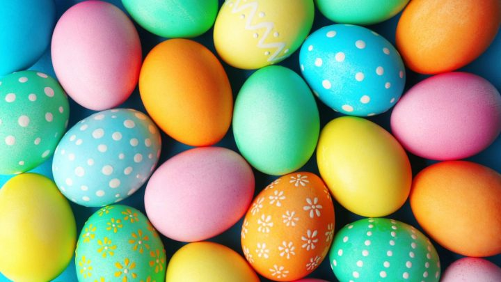 Image of a large collection of Easter Eggs in a multitude of pastel Easter colors - pink, blue, green, yellow and orange.
