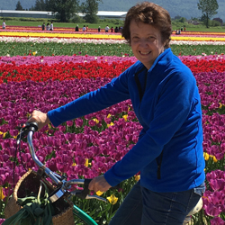 Kathie smiles on a bicycle while behind her rows of pink, red, purple, and yellow flowers bloom in the afternoon sun.