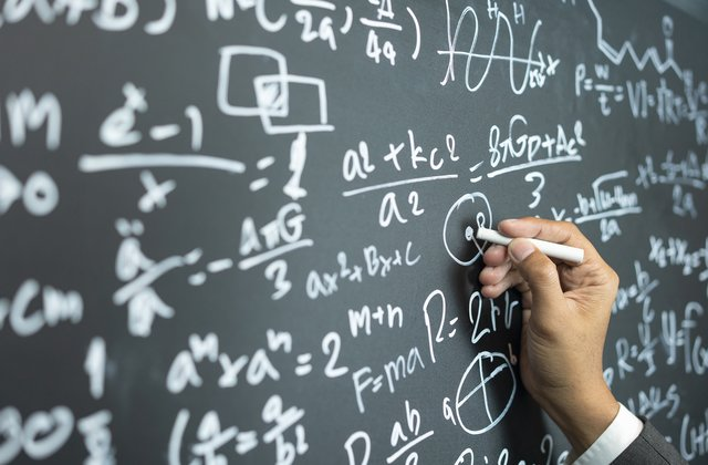 Image of a hand writing on a blackboard that is filled with various different Math equations.