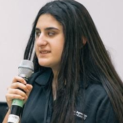 Nika holds a microphone as she speaks at a Volunteer event.