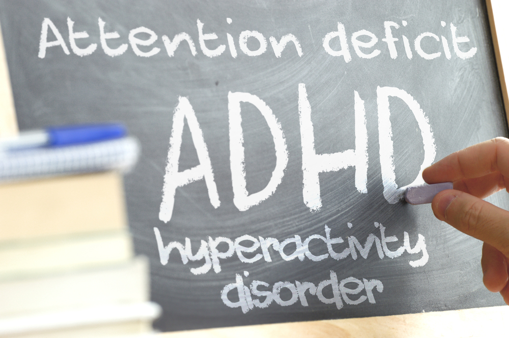 A hand holding a piece of chalk writes on a blackboard which reads ADHD Attention Deficit Hyperactivity Disorder