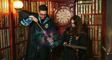 Two young people dressed in wizarding robes and wearing Harry Potter glasses work together to try to find their way out of what looks to be a library.
