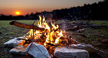 A small campfire burns brightly as a darkened line of trees extend into the distance and a bright orange sun sinks into the horizon.