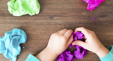 A pair of child's hands molds a large piece of purple clay as pink and green and blue lumps of clay also sit at the ready.