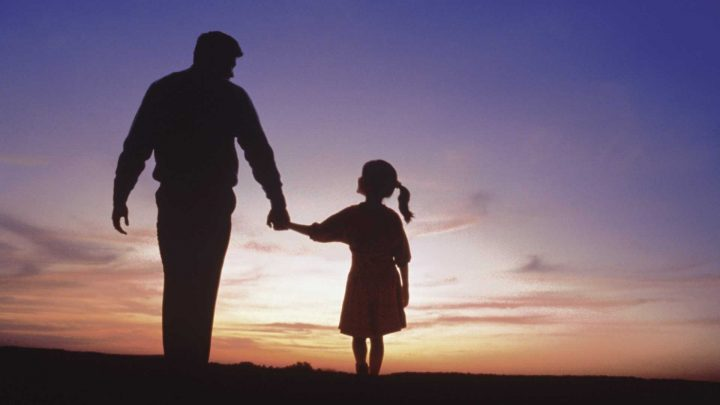 A father and daughter hold hands and walk, silhouetted by the a purple and orange dusk sky.