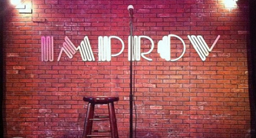 """Image of an empty stage at a comedy club, a microphone stand and a stool sit in the center while the words """"Improv"""" are imprinted on a red brick wall that serves as a backdrop."""