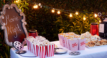 """A table is adorned with popcorn boxes and other various snacks while a elaborate blackboard has """"Movie Night"""" written in chalk."""