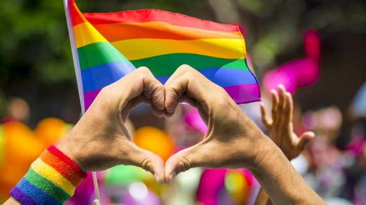 A pair of hands form the universal symbol for a heart or love in front of a rainbow Pride flag that is blowing in the wind.