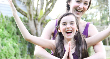 A young girl and her mother strike up several yoga poses together, smiling and laughing as they hold the pose.