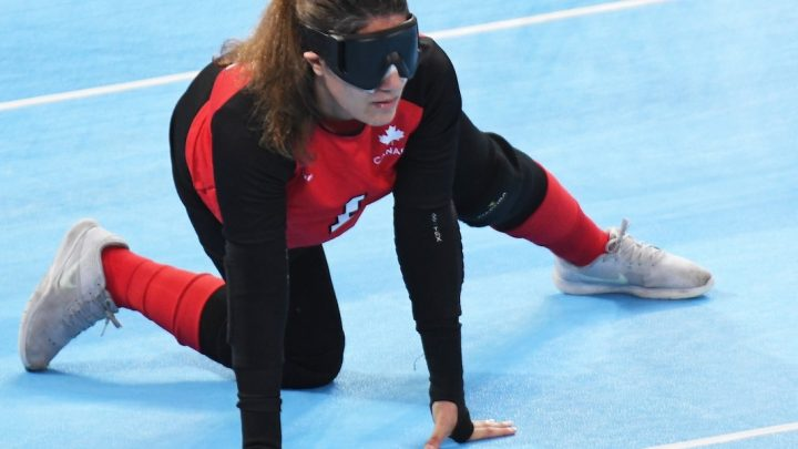 Image of Maryam Salehizadeh wearing Team Canada uniform on the Goalball playing field, crouched in a defensive position.