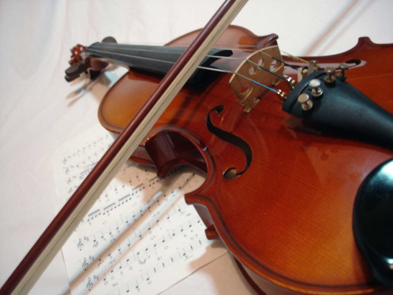 Image of a violin with its bow lying across the top of it as it sits on a table covered in sheet music.